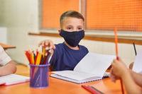 Kind mit Mundschutz beim Lernen in der Grundschule