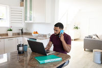 Man talking on smartphone while using laptop at home