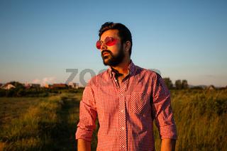 Man in pink glasses enjoying sunny weather