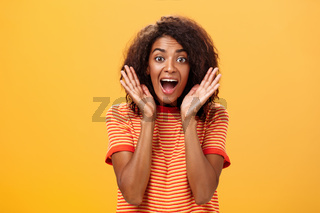 Waist-up shot of impressed excited talkative dark-skinned woman with curly hair and perfect skin yelling from happiness and amazement shaking palms near face cheering for awesome sale over orange wall