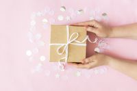 Hands holding paper gift box with ribbon, star, circle paper confetti, glitters