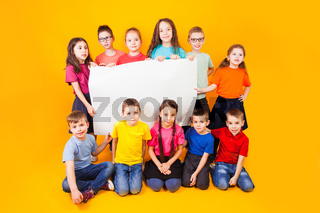 The group of kids holding a big white copy space poster