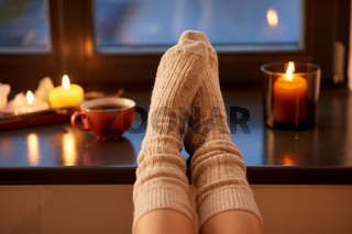 Legs in socks on window sill at home in autumn