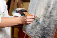 Close-up of an unrecognizable woman painter doing a brush stroke