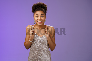 Excited lucky hopeful charming african american female model hopes win competition cross fingers dreamy smiling optimistic believe fortune praying dream come true, make wish blue background