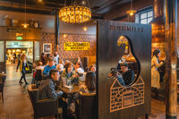 Tourists visiting Old Bushmills Distillery and tasting Irish whiskey in a bar