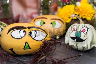 Halloween-Dekoration - verschiedene Zierkürbisse mit Gesichtern bemalt