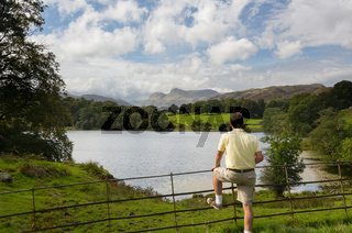 Hiker overlooks Loughrigg Tarn in Lake District