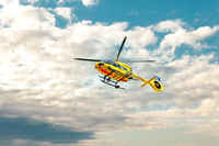 ADAC Notarzt, Paramedic rescue helicopter against blue cloud sky.