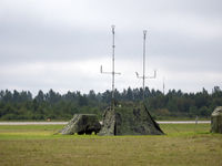 Military tent with radio and antenna camouflage net