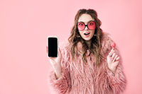 Surprised hipster woman holding blank screen mobile phone over pink background