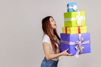 Side view portrait of woman holding stack of presents in hands, having excited facial expression.