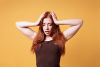 stressed exhausted young woman holding head suffering from headache or nervous breakdown