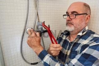 Klempner mit Rohrzange montiert neuen Brauseschlauch