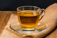 Side view of a cup of hot tea on sack cloth.
