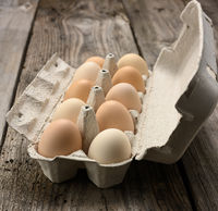 fresh whole brown eggs in paper packaging on a gray wooden background, close up