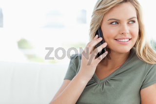 Woman smiling as she makes a call and looks to the side