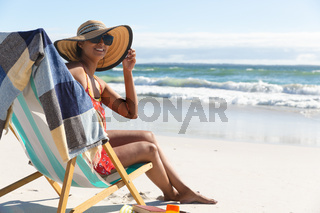 Portrait of smiling mixed race woman on beach holiday sitting in deckchair