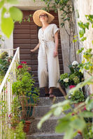 Beautiful female tourist wearing big straw sun hat and sundress standing on old vintage stone house staircase during summer travel on Mediterranean cost on hot summer day.