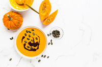 Homemade pumpkin soup with pumpkin oil and seeds on marble background