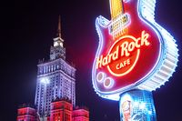 Warsaw, Poland, Nov 17, 2018: Neon light logo of Hard Rock Cafe and exterior near Palace of Culture and Science.