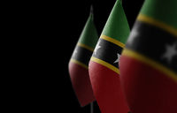 Small national flags of the Saint Kitts and Nevis on a black background