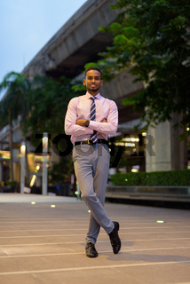Full length portrait of handsome young African businessman outdoors in city at night