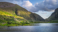 Mountains and Black Lake illuminated by sunlight at sunset in Gap of Dunloe, Black Valley
