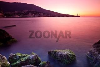 Rocky beach sunrise over sea