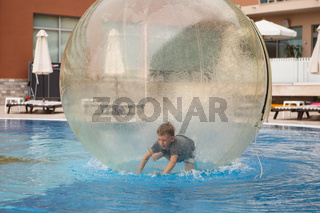 Little boy have fun inside big plastic balloon on the water of swimming pool on the summer resort. Kid inside big inflatable transparent ball running and having fun.