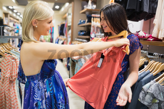 Woman holding shirt up to friend