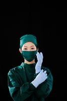 A young female surgeon wore surgical gloves