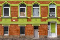 Fassade eines Hauses in den Farben Gruen-Orange