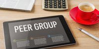 A tablet on a desk with the headline Peer Group