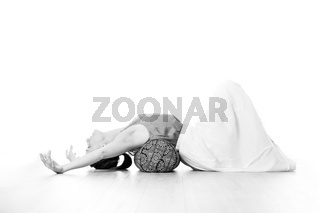 Restorative yoga with a bolster. Young sporty attractive woman in bright white yoga studio, stretching and relaxing during restorative yoga with bolster cushion. Healthy active lifestyle
