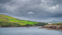 Fishing or tour boats returning to Dingle harbour guided by lighthouse