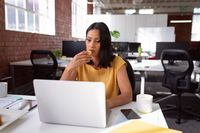Caucasian businesswoman sitting at desk with coffee using laptop and biscuit