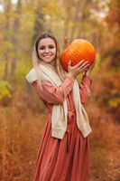 Young witch with jack o lantern in forest
