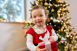happy baby girl with christmas gift at home