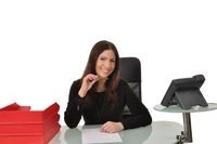 Mitarbeiterin sitzt an einem Schreibtisch mit einem Telefon