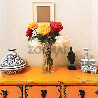 Bouquet of fresh multicolored rose flowers in glass vase on yellow vintage table with buddha head