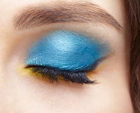Closed human female eye with blue smoky eyes shadows and yellow liner.