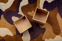 Two open cardboard boxes on camouflage background