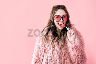 Fashion portrait of pretty hipster woman holding lollipop and looking to camera