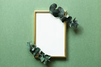 Empty photo frame with eucalyptus leaf on green background. top view, copy space