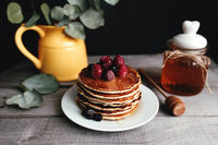 Juicy pancakes with berries and honey on a white plate, spoon, jar, wooden table