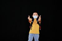 A little boy with a mask held out his thumb