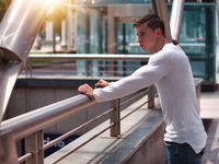 Muscular young man with white shirt in city setting