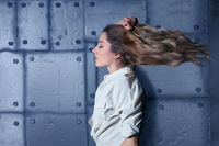 Portrait of young beautiful blonde woman with flying hair on metal wall background.