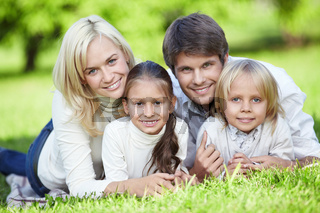 Young parents with children on the grass